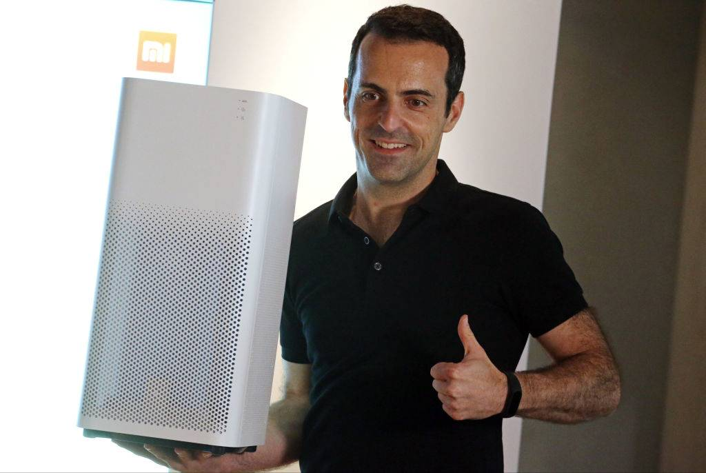 A man hold up an air filter while giving a thumbs up.
