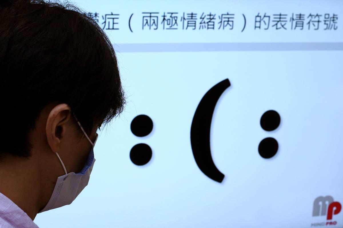 A bipolar man stares at a symbol that represents smiling and frowning.