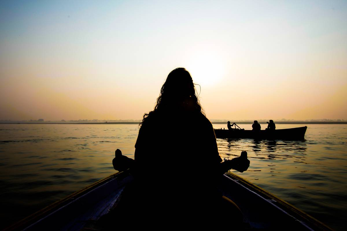 A woman meditates on a boat.