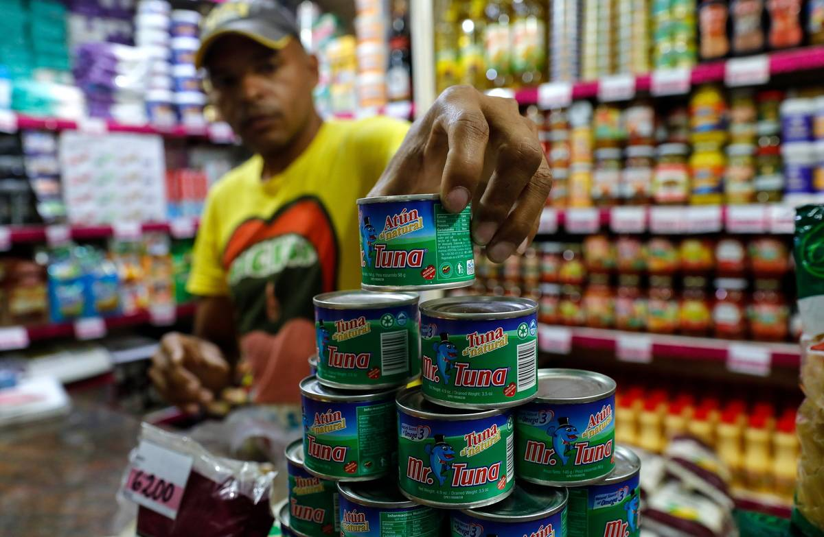 A grocery store employee stacks tuna cans.