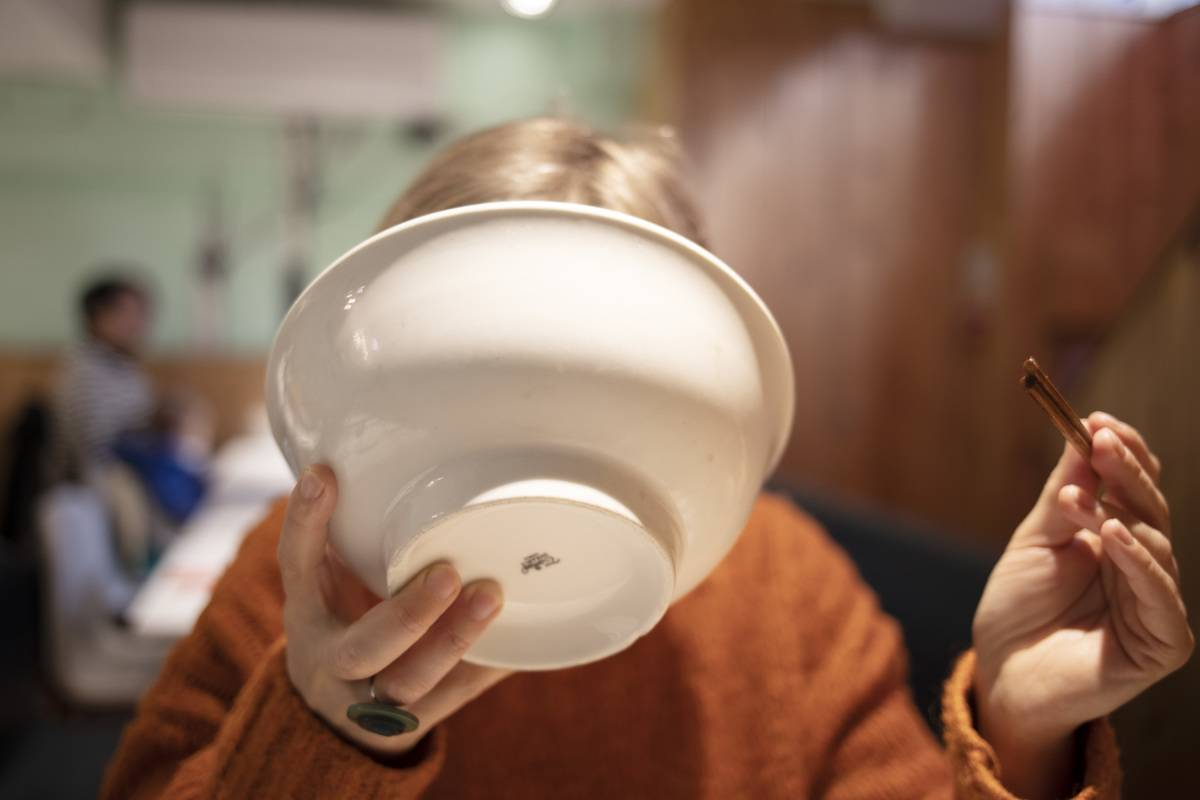 Woman tipping a bowl to her face to drink the broth