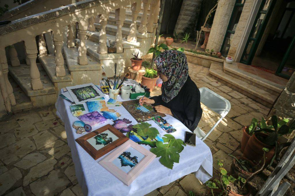 A woman paints art on leaves.