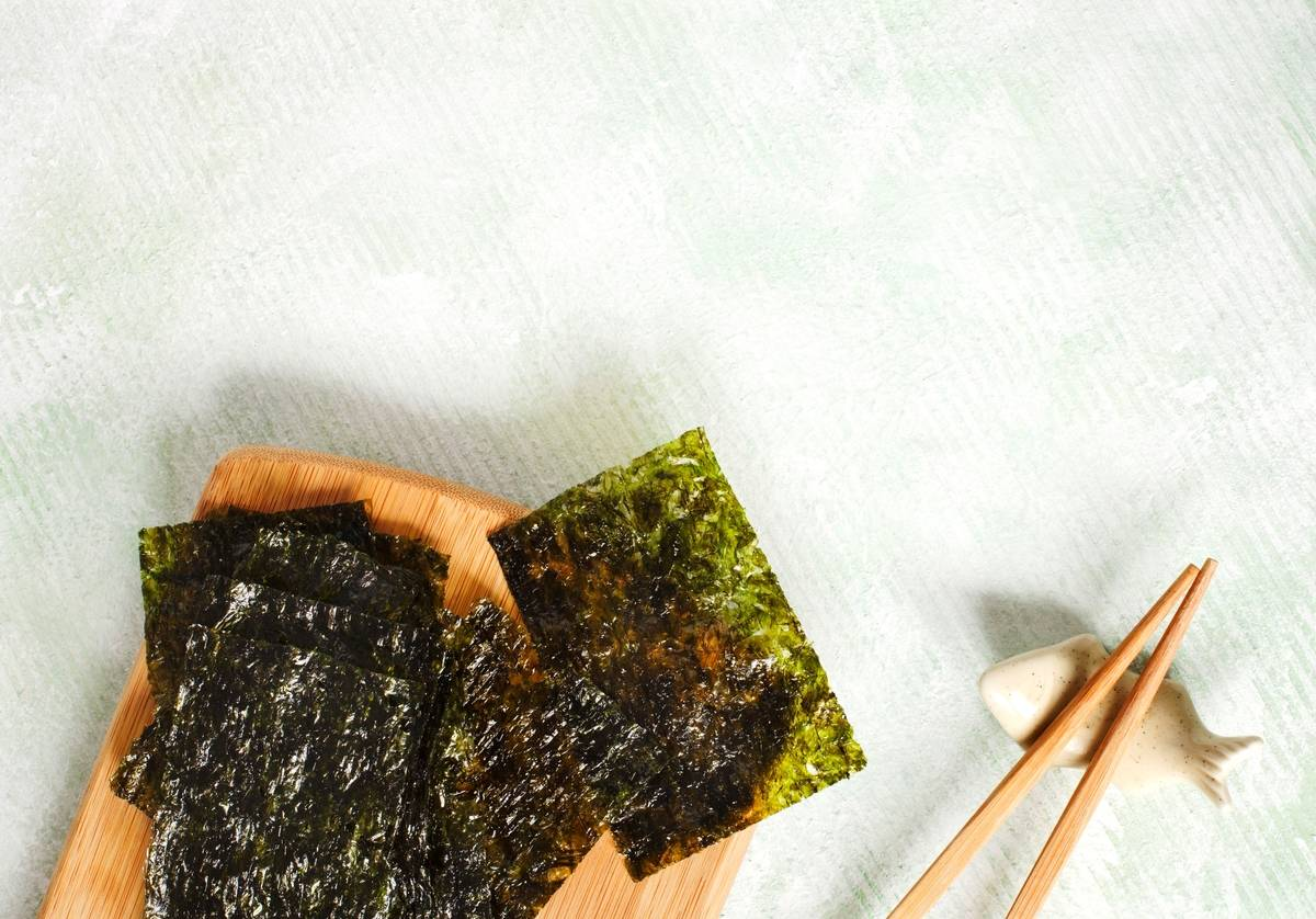 Roasted seaweed is served on a wooden board with chopsticks.