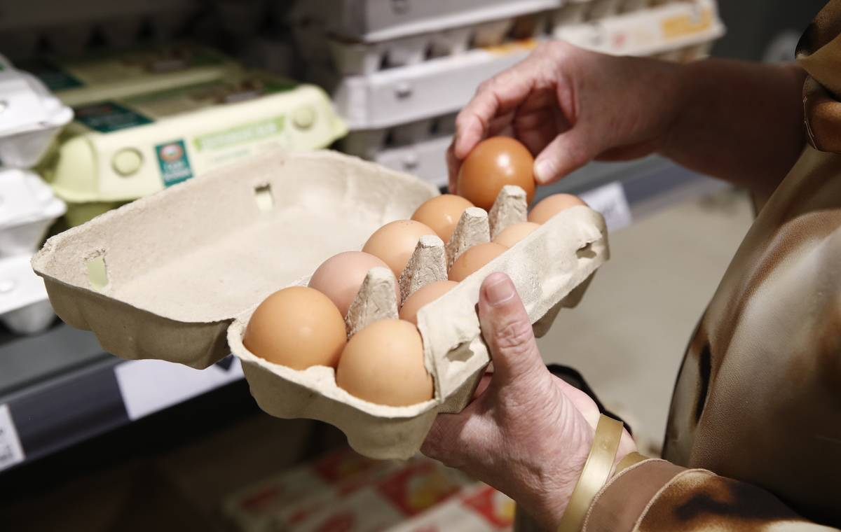 A customer checks eggs at a supermarket.