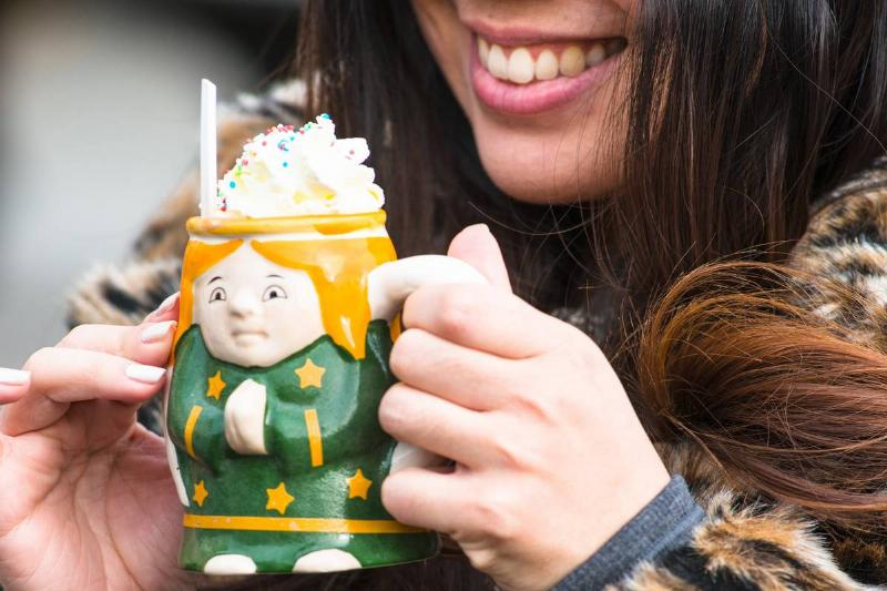 A woman enjoys hot chocolate in a Christmas ceramic mug.