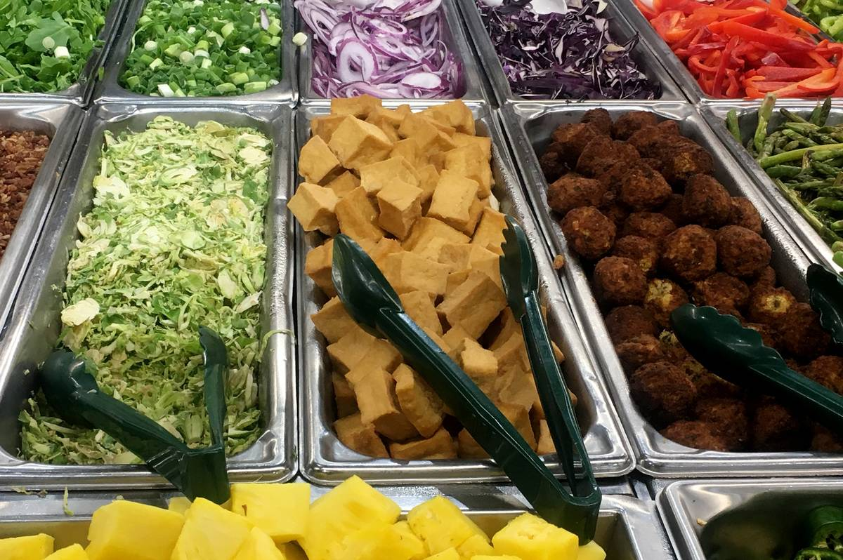 Vegan and vegetarian food are offered at a buffet.
