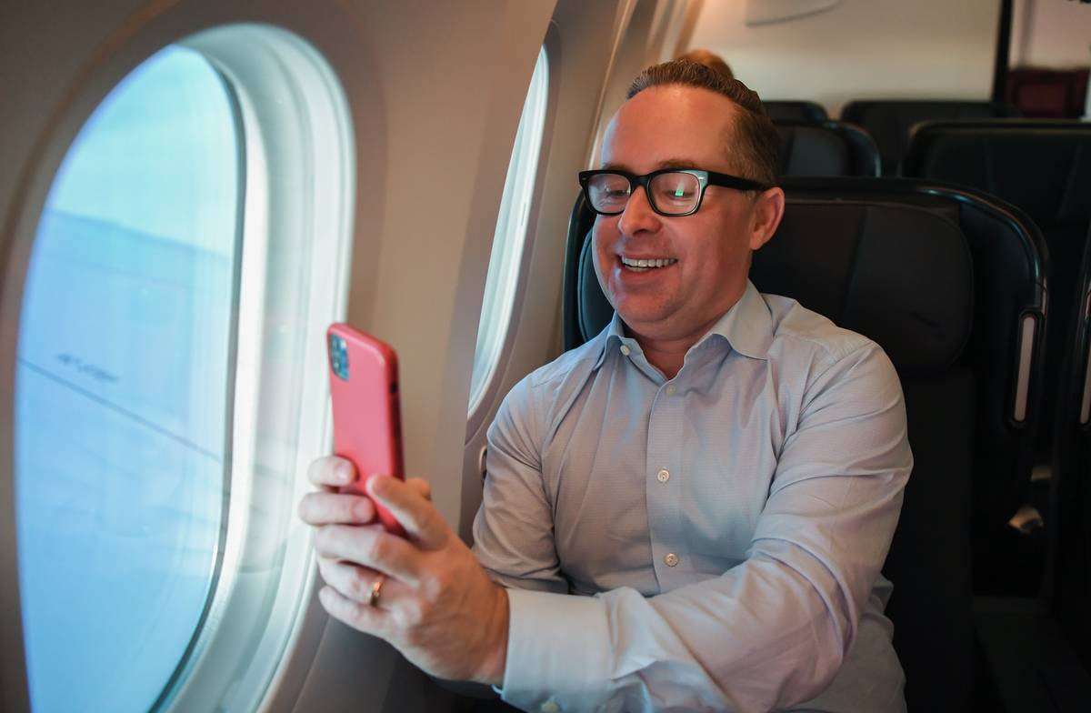 A man smiles while on his phone in an airplane.