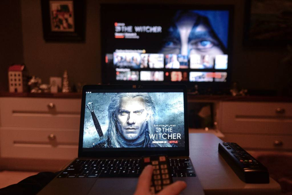 A person streams Netflix on their laptop and television.