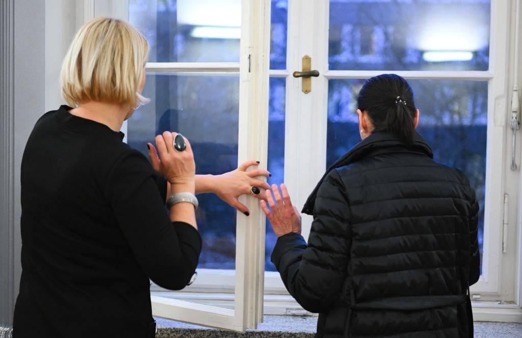 Two women close a window.