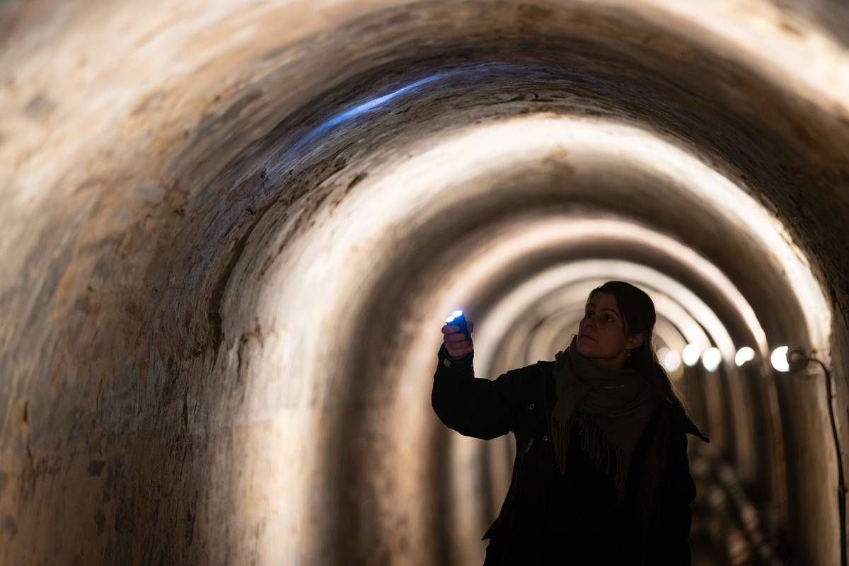 A woman searches a museum tunnel for bats with a flashlight.