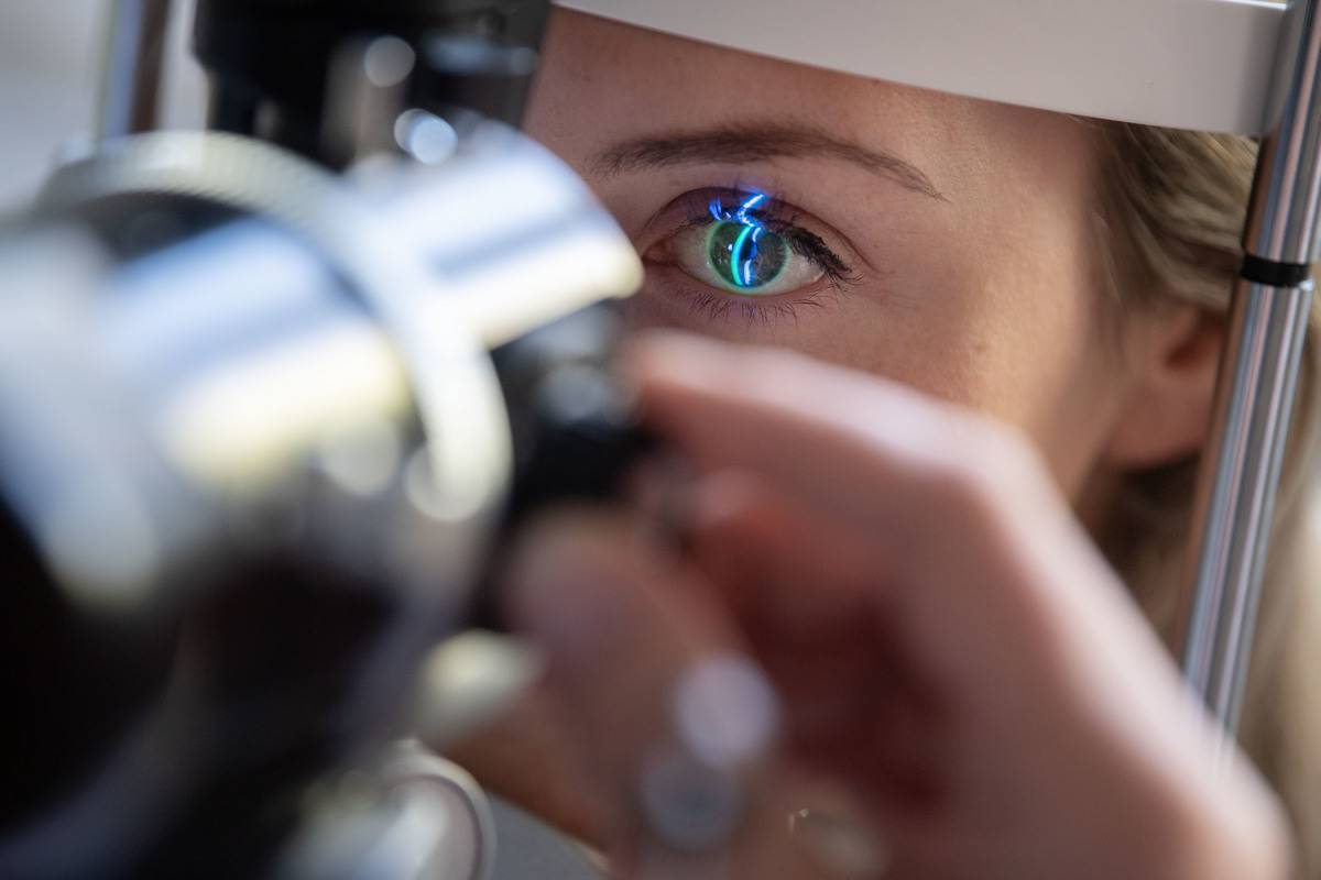 A doctor examines the eye of a patient.