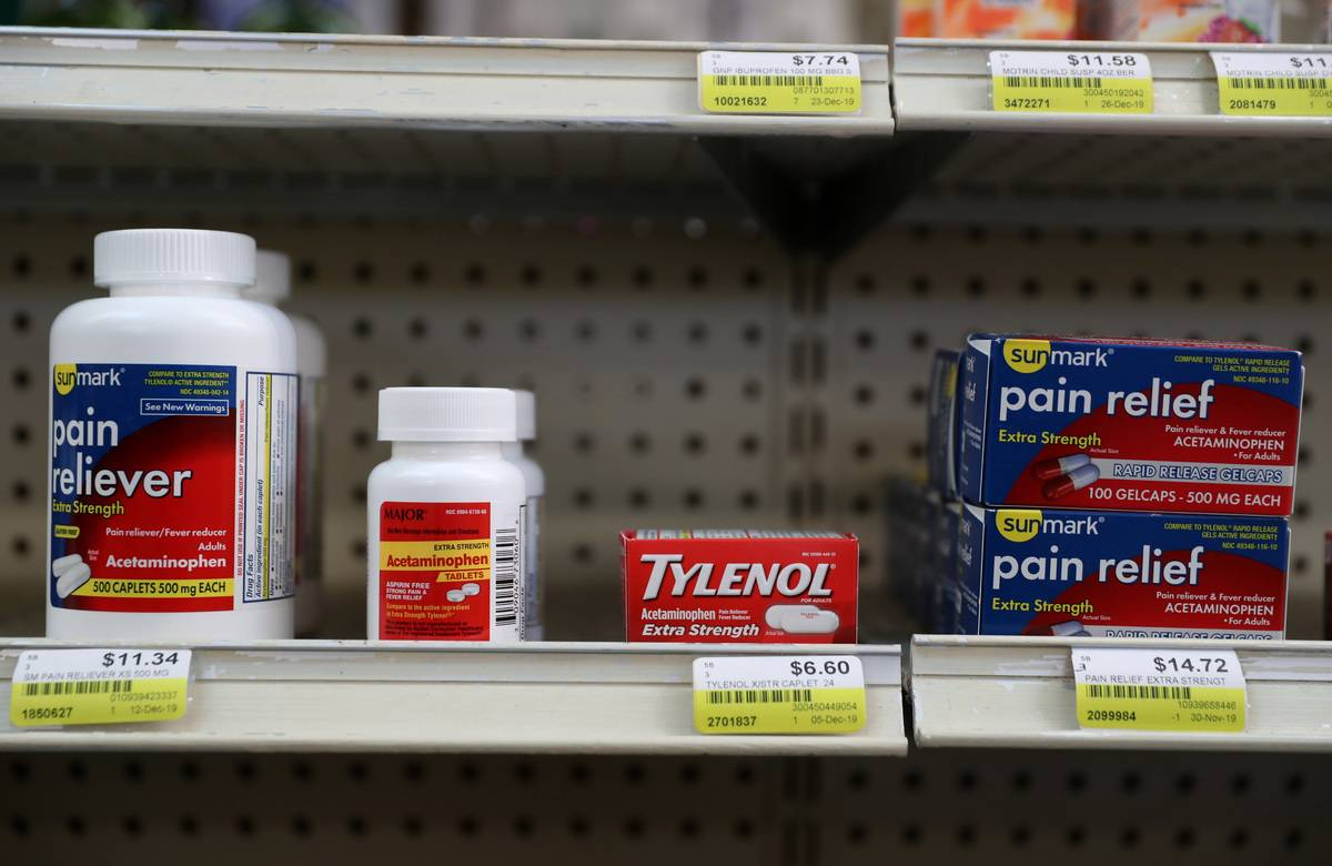 Tylenol and Ibuprofen sit on a shelf in a pharmacy.