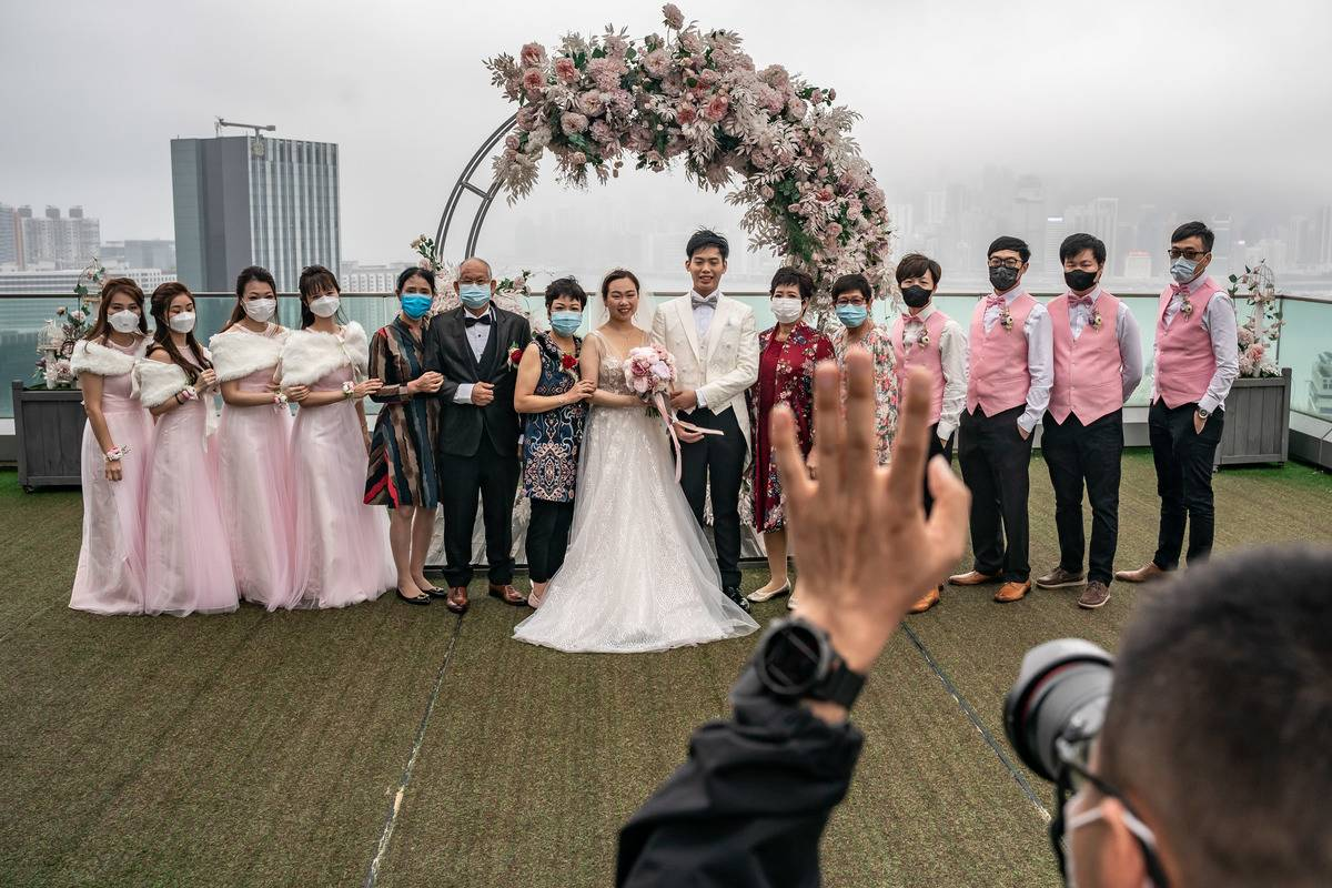 Newly-weds in Hong Kong post for a photo while wearing face masks for social distancing.