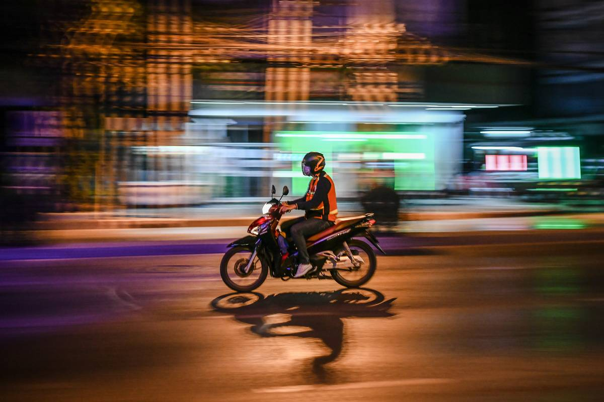 A motorcyclist rides on the street during night hours In Bangkok.