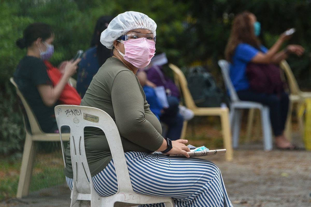Residents of the Phillippines wear face masks while sitting in chairs.
