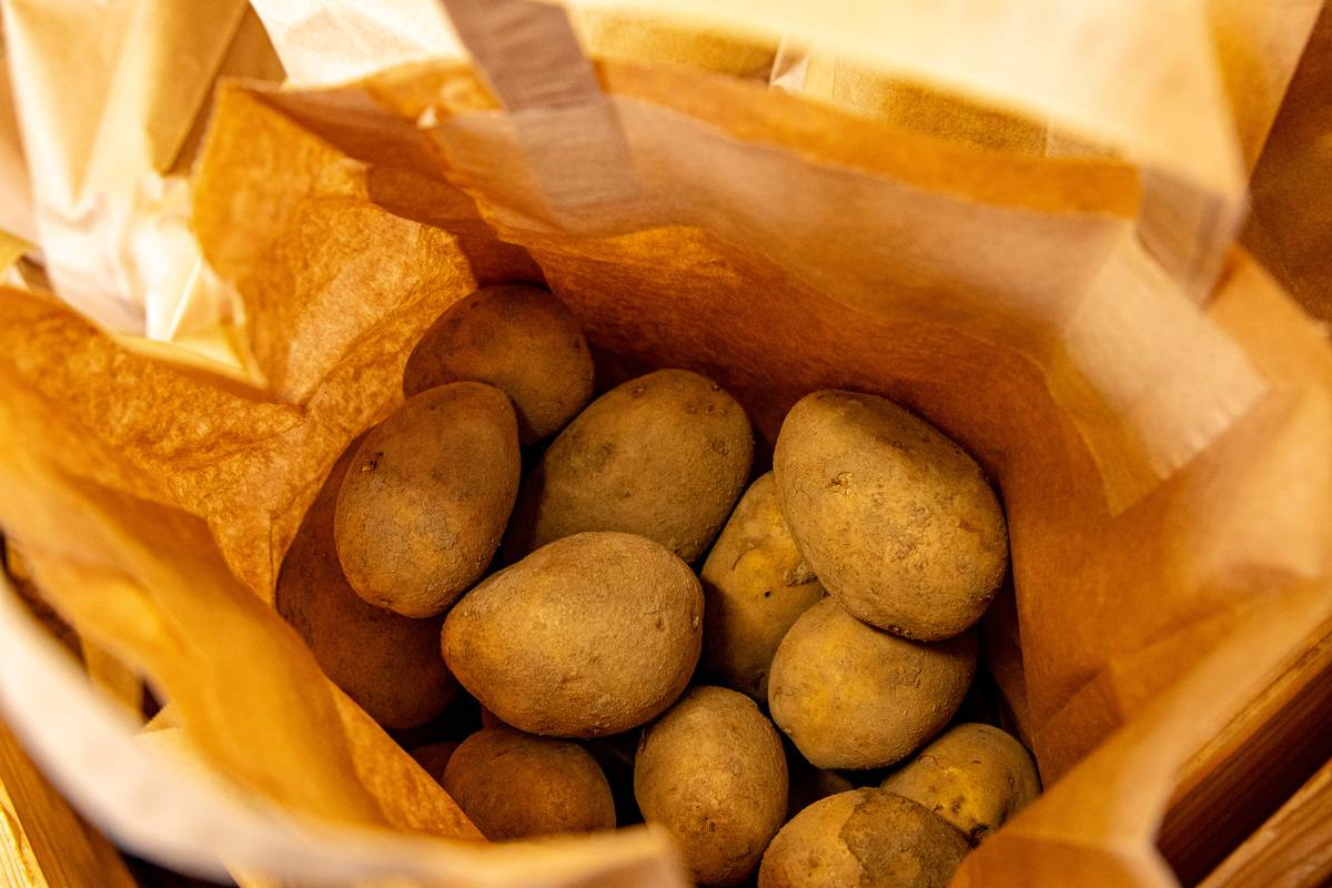 Potatoes are in a brown paper bag.