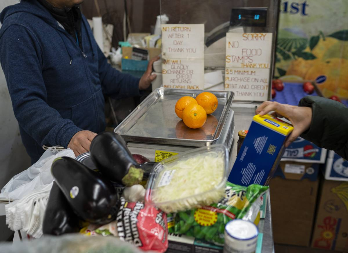 A customer buys fresh oranges with other food at a supermarket.