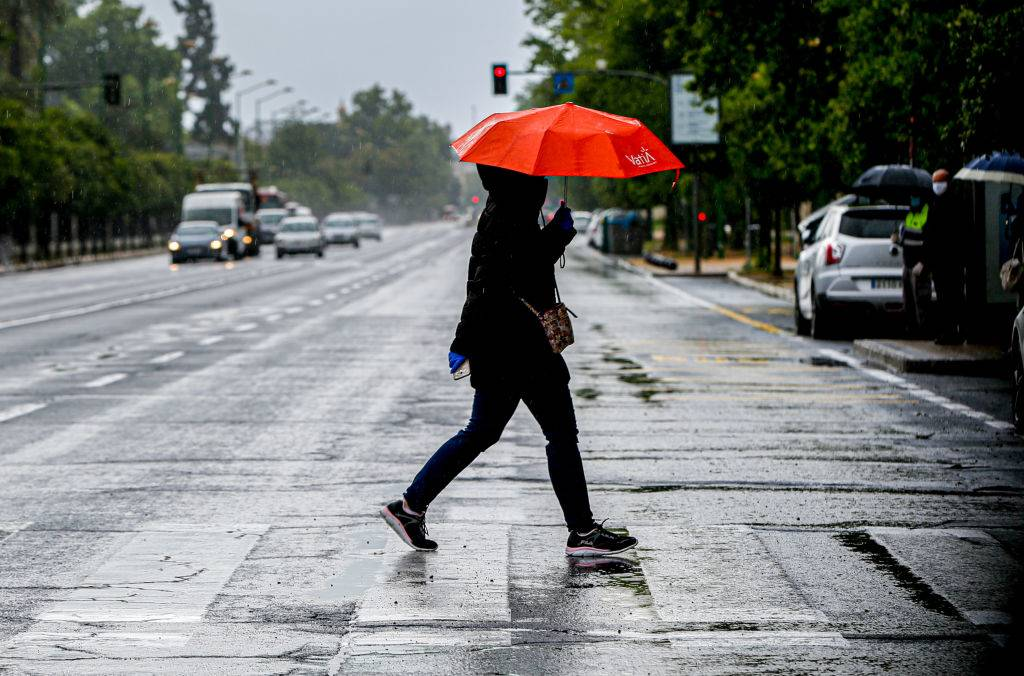 A woman walks across the street in the rain.