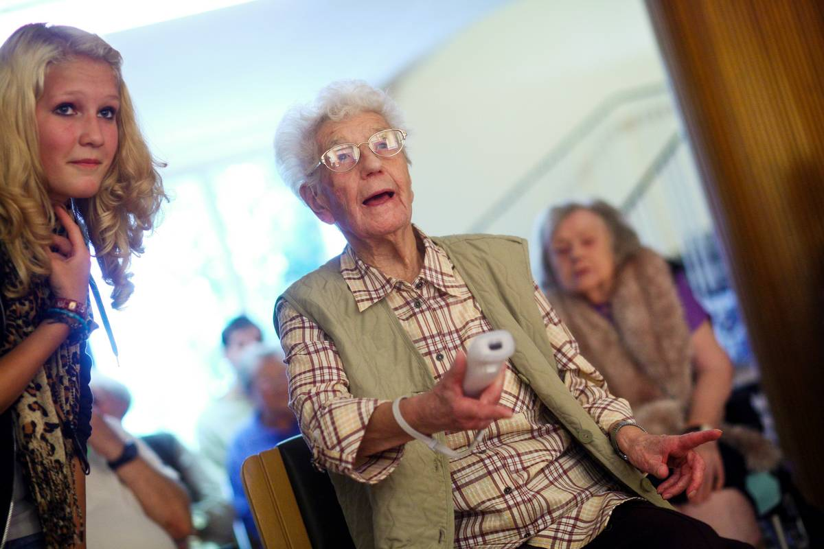An elderly lady plays Wii Sports with a young woman.