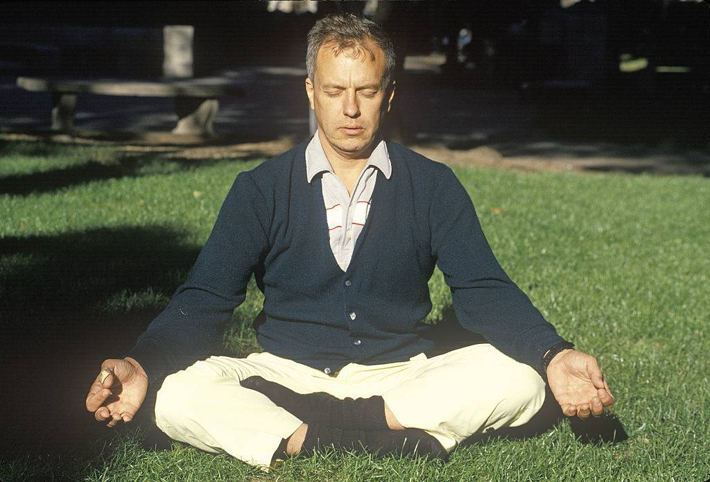 A man meditates in the grass.
