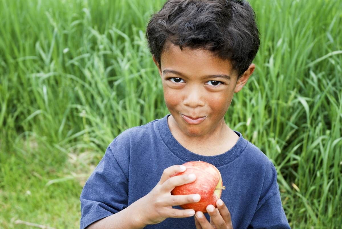 A boy eats an apple.