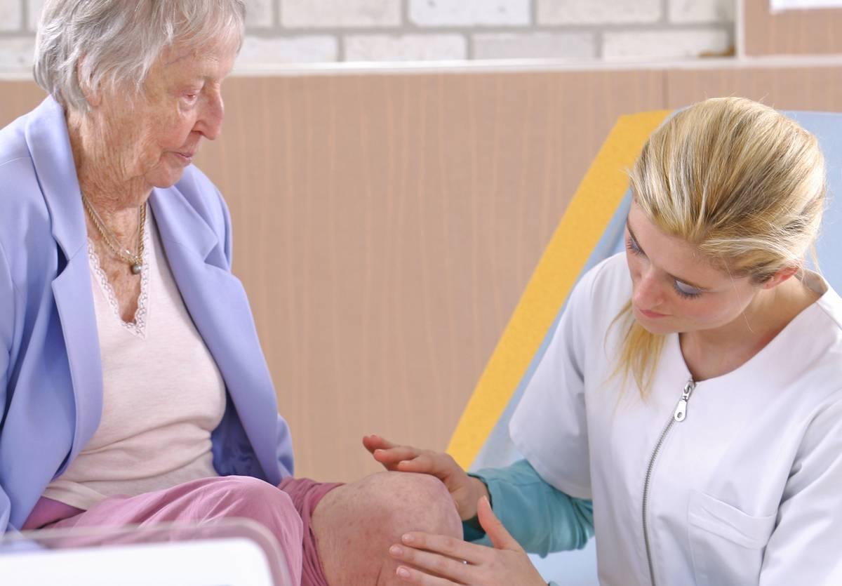 A nurse examines a patient's knee.