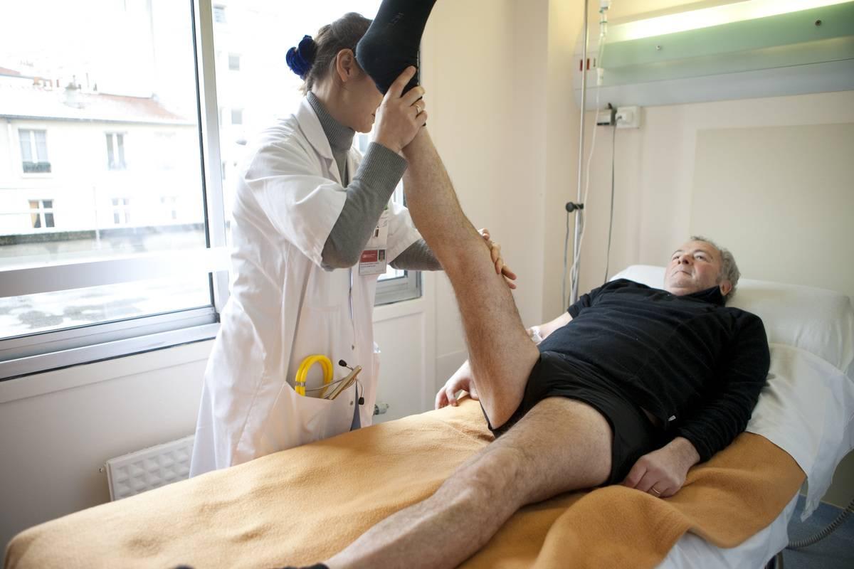 A rheumatologist examines a patient's hip flexibility.