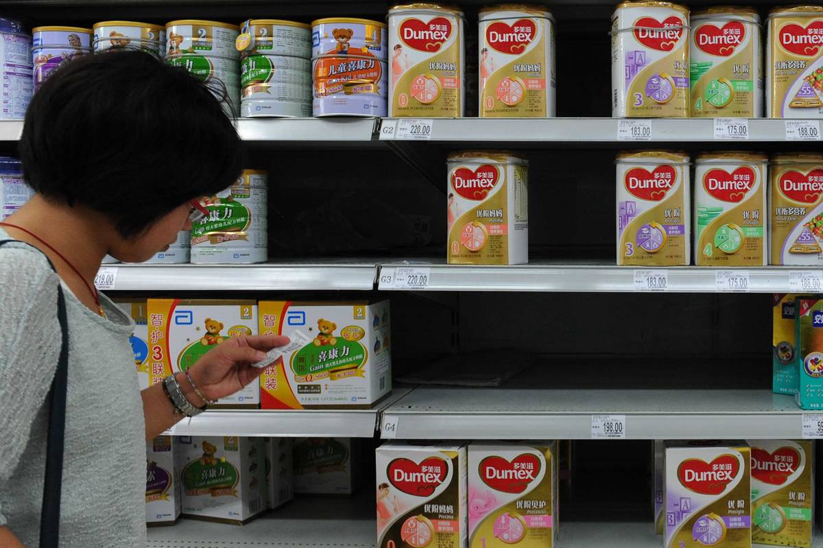 A woman checks the price beside a shelf of Dumex baby formula