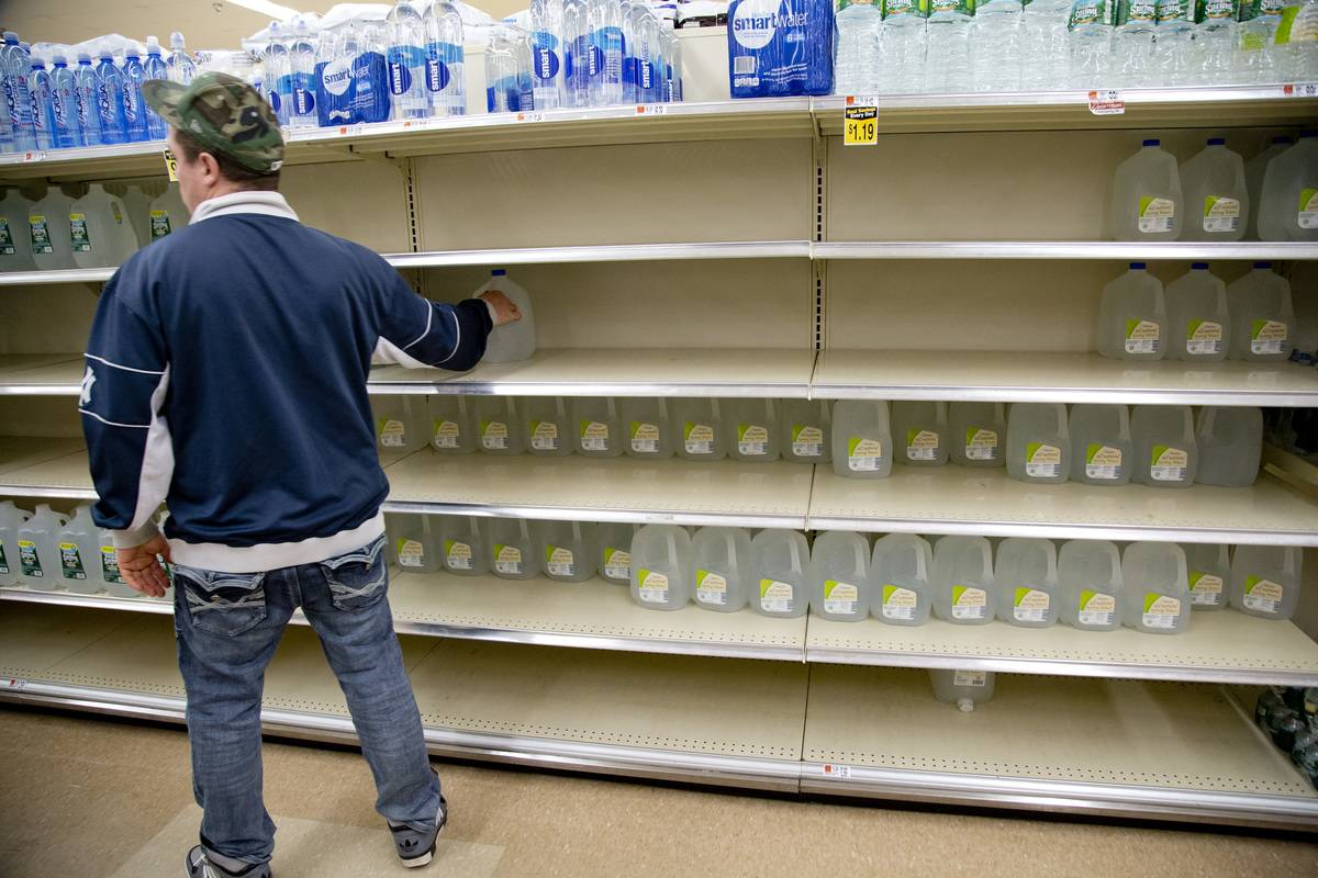 A man grabs a gallon of water off the shelf before a big winter storm hits.