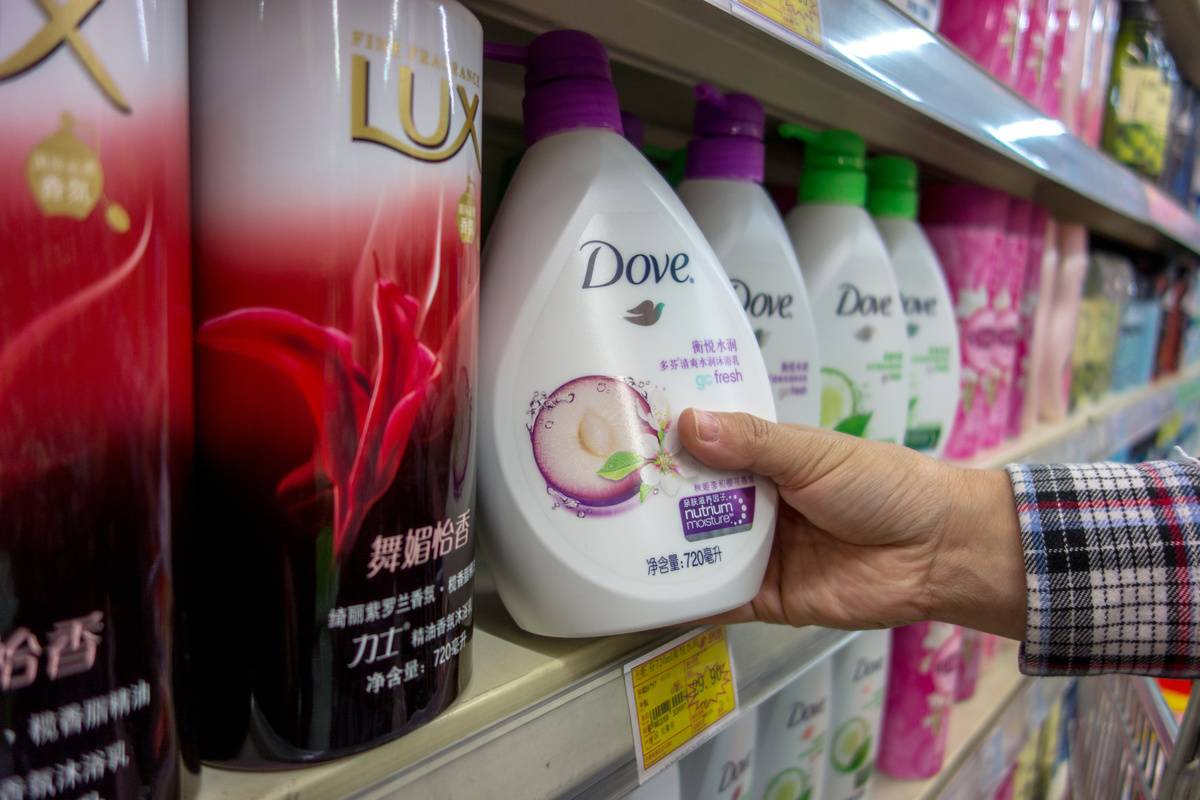 A consumer picks a bath soap from a grocery store shelf.