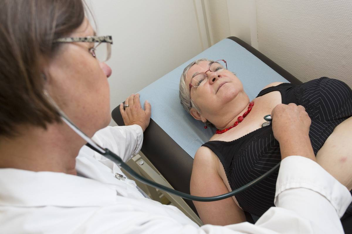 A doctor measures a woman's heartrate.
