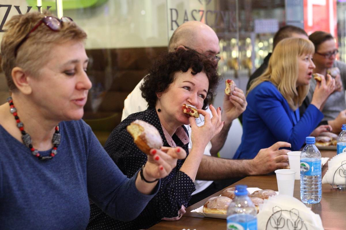 Adults compete in the donut fast eating championships.