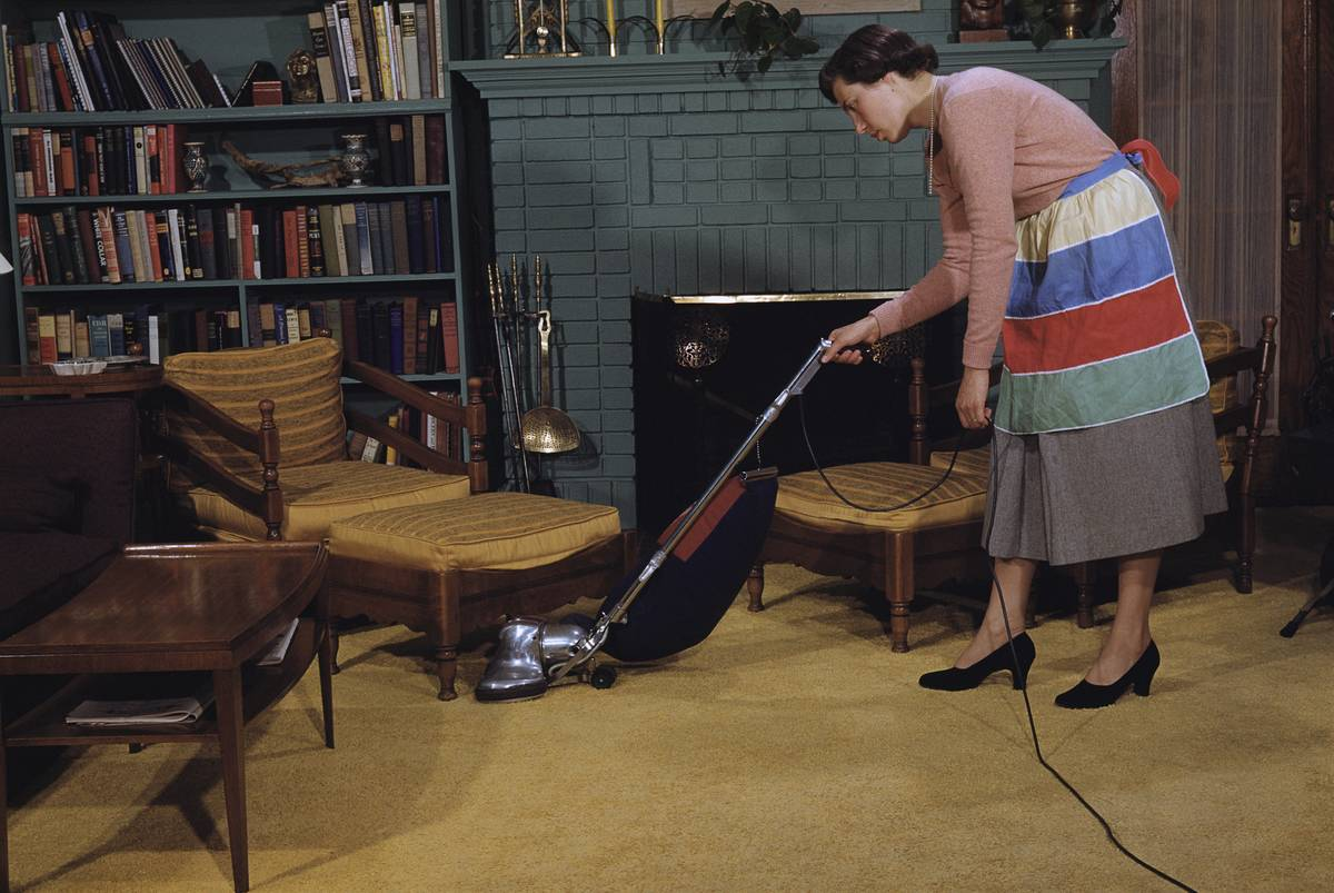 A woman vacuums in her living room.