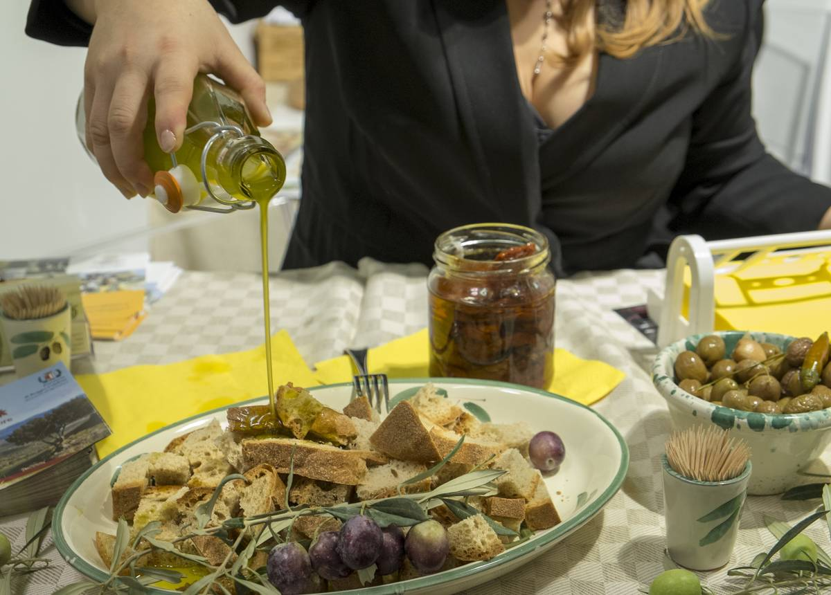 A woman pours olive oil onto wholegrain part in Italy.