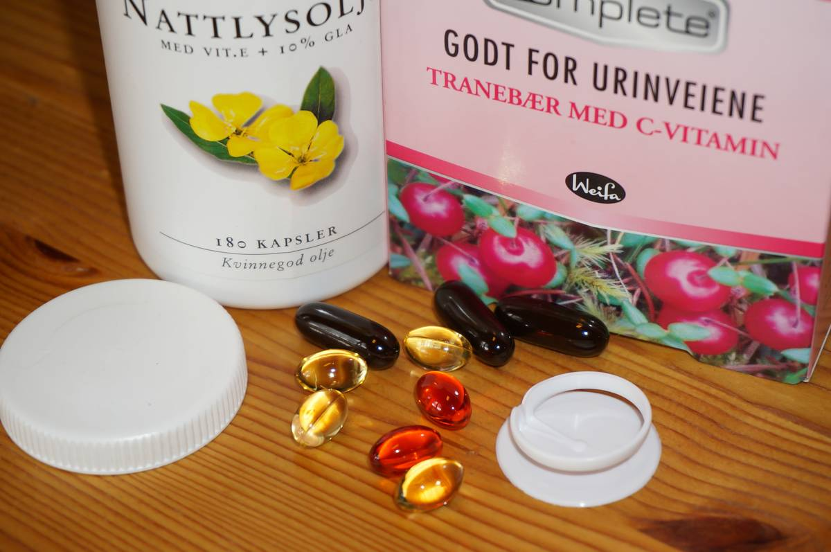 Several vitamin pills sit next to plastic containers.