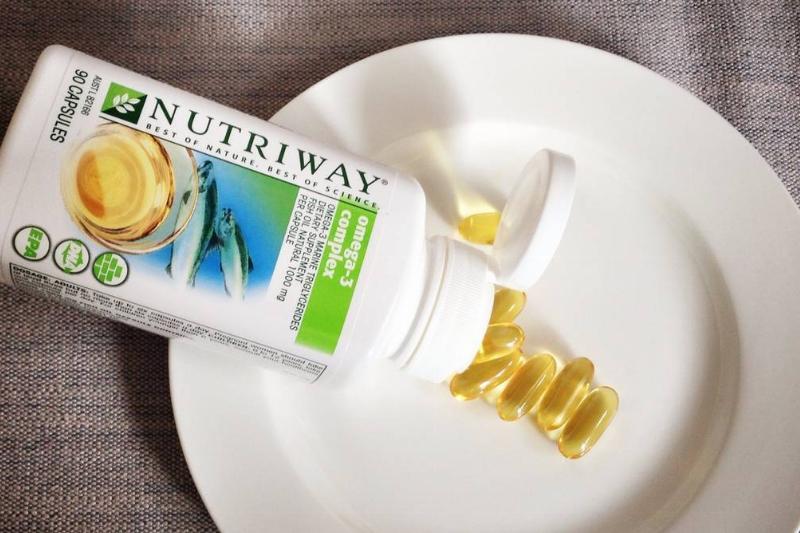 Omega-3 fatty acid supplement pills spill onto a plate.