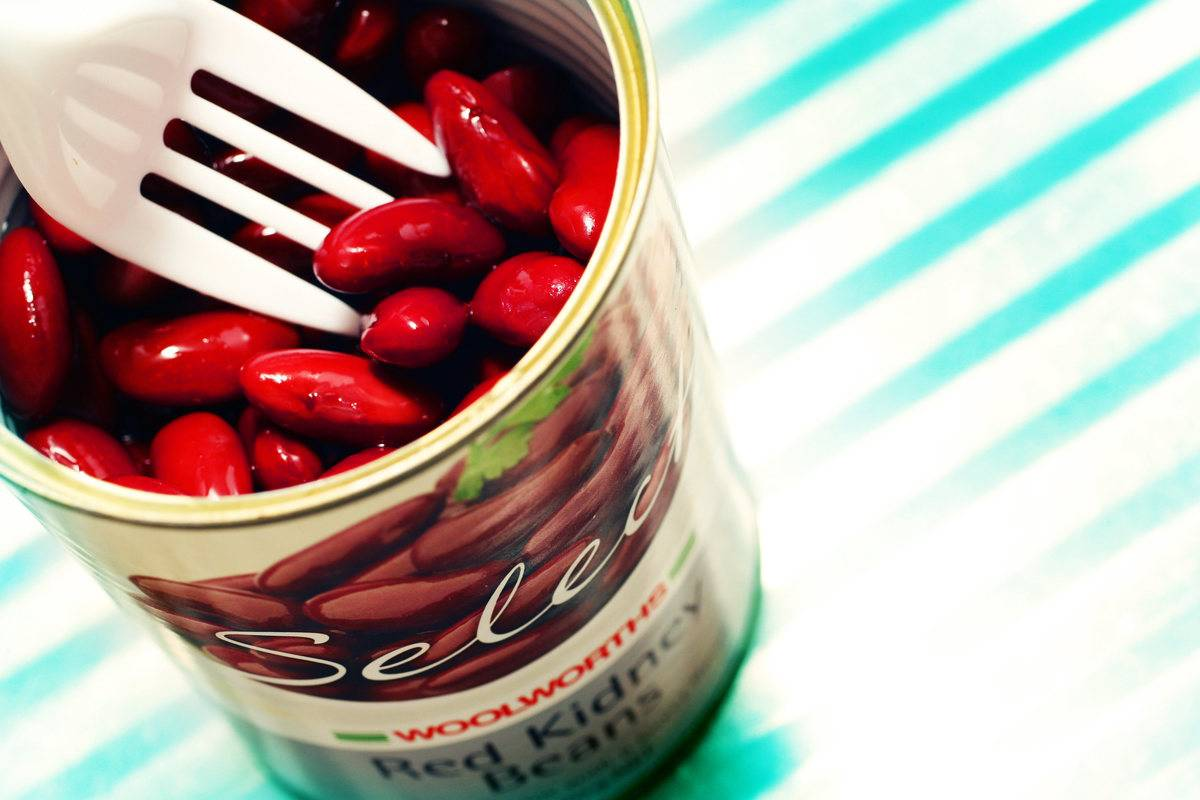 A plastic fork digs into a can of kidney beans.