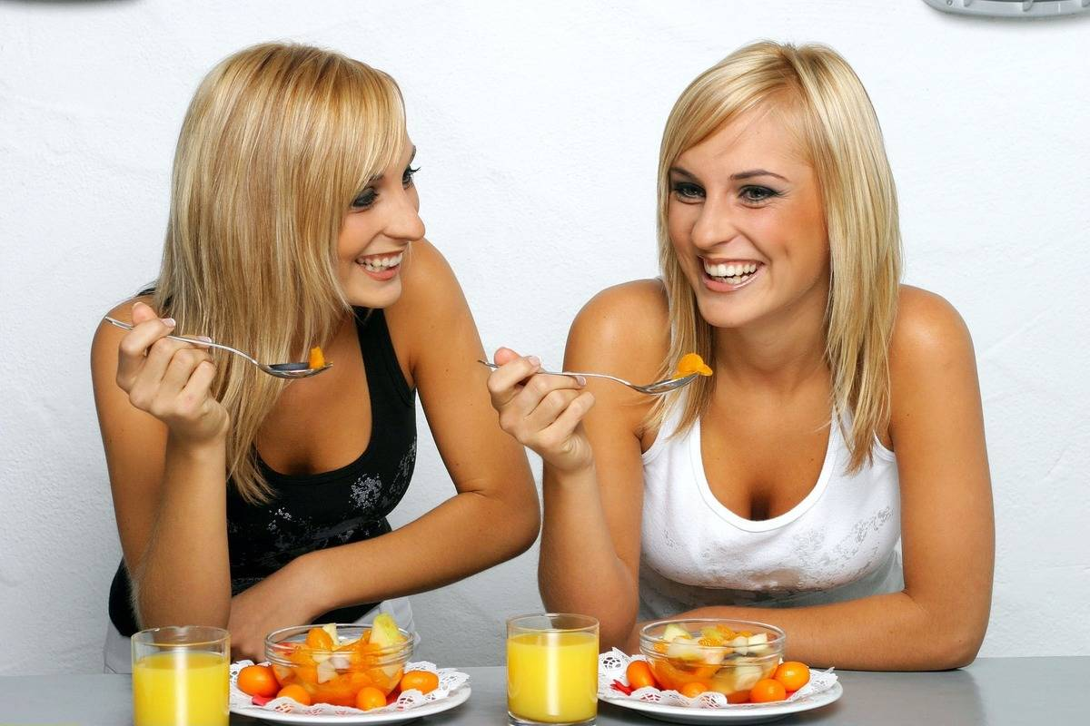 Two women enjoy eating a fruit salad.
