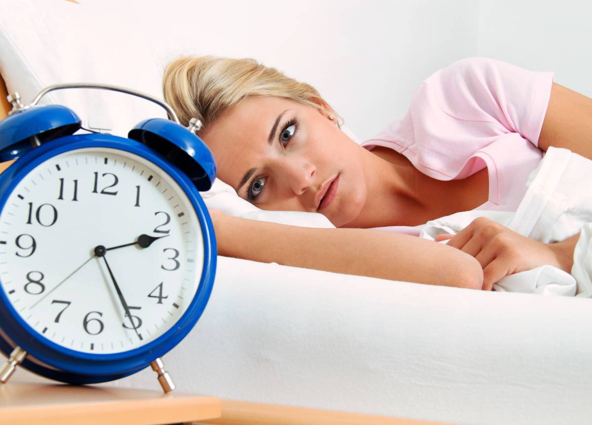 A woman stars at her clock as she struggles to sleep.