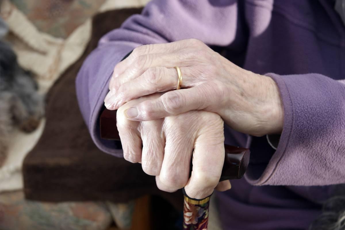 An elderly woman clutches a walking stick.