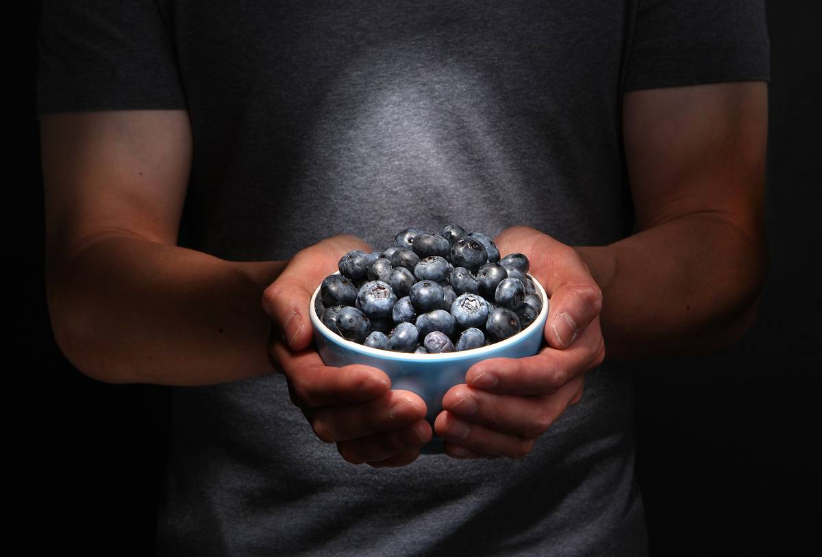 A man holds a cup of blueberries.
