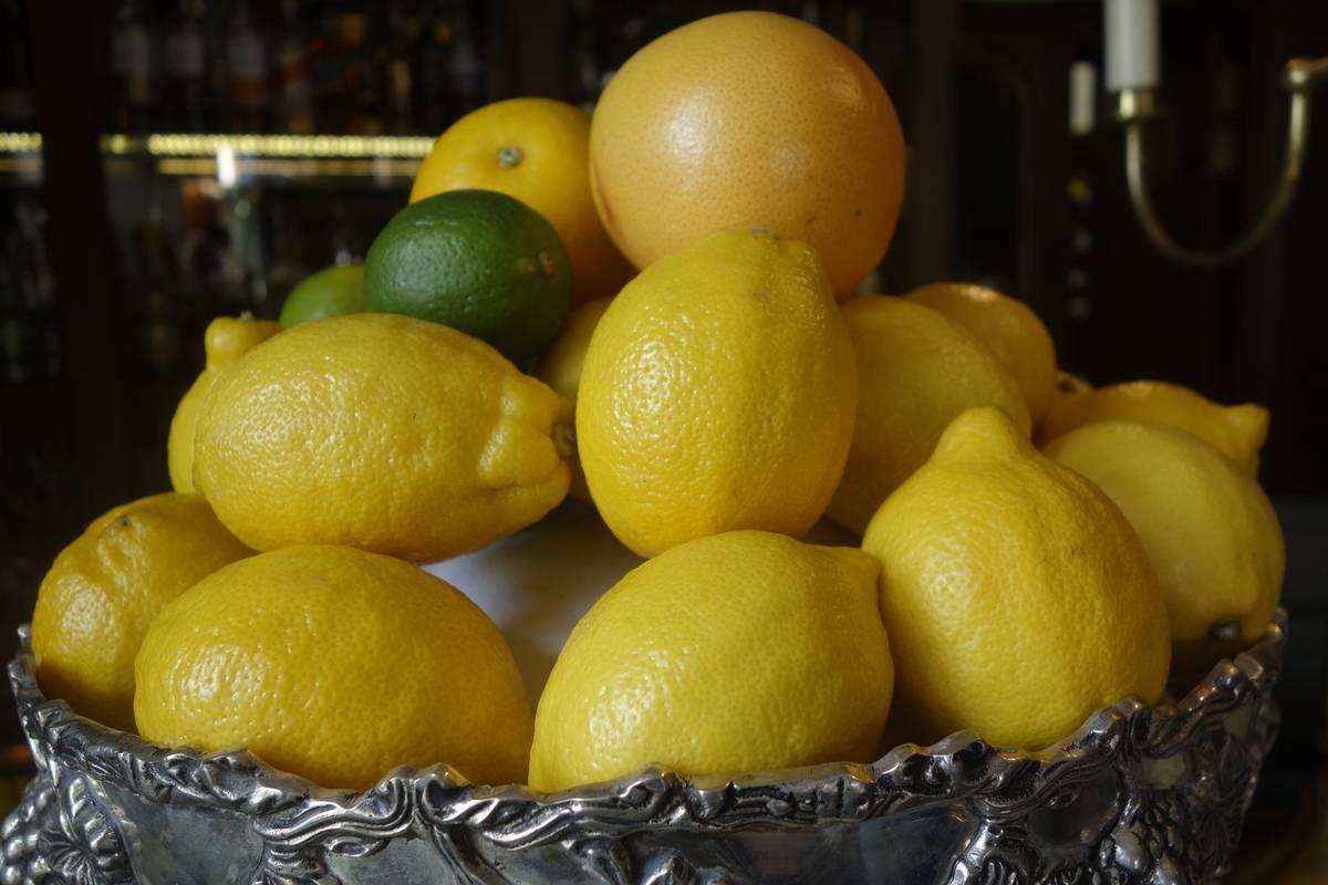 A bowl holds lemons, limes, and a grapefruit.