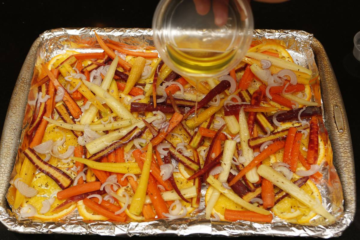 A person pours olive oil onto a pan of carrots to roast.