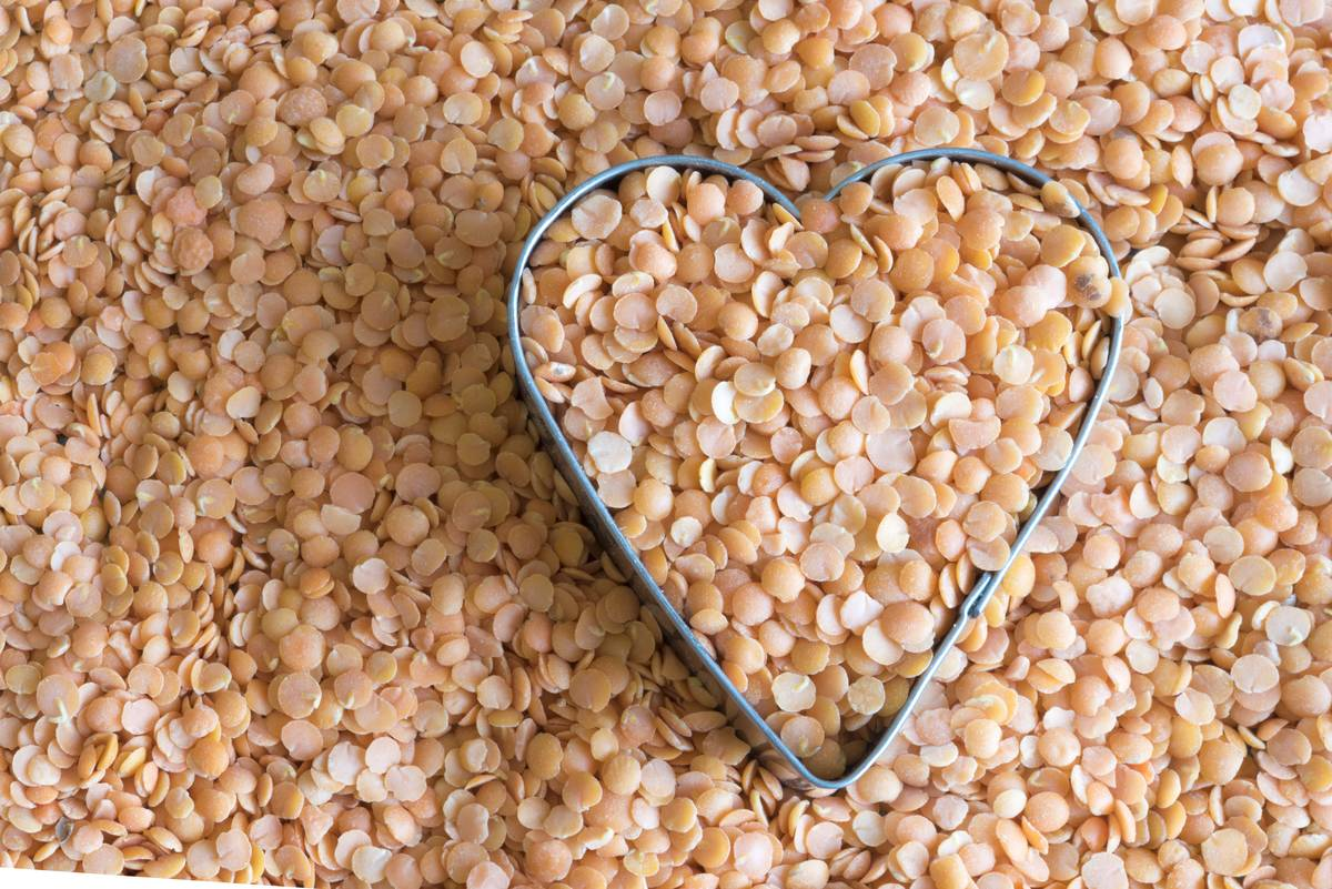 Yellow and orange split peas are arranged in a heart-shaped cookie cutter.