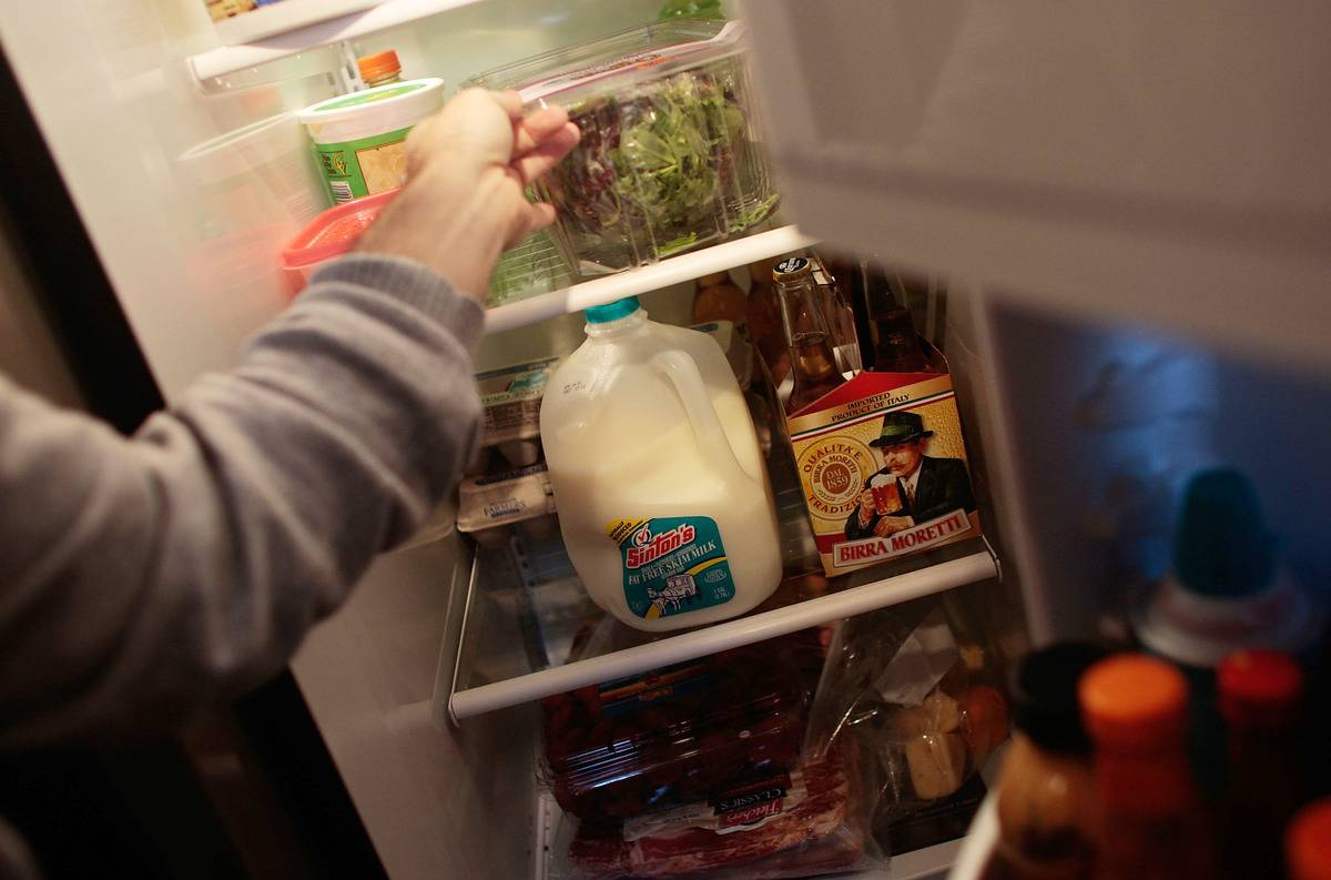 A person opens the fridge to reveal a carton of milk.