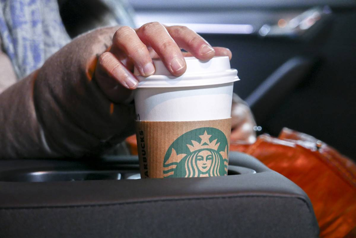 A person holds a starbucks cup in their car.