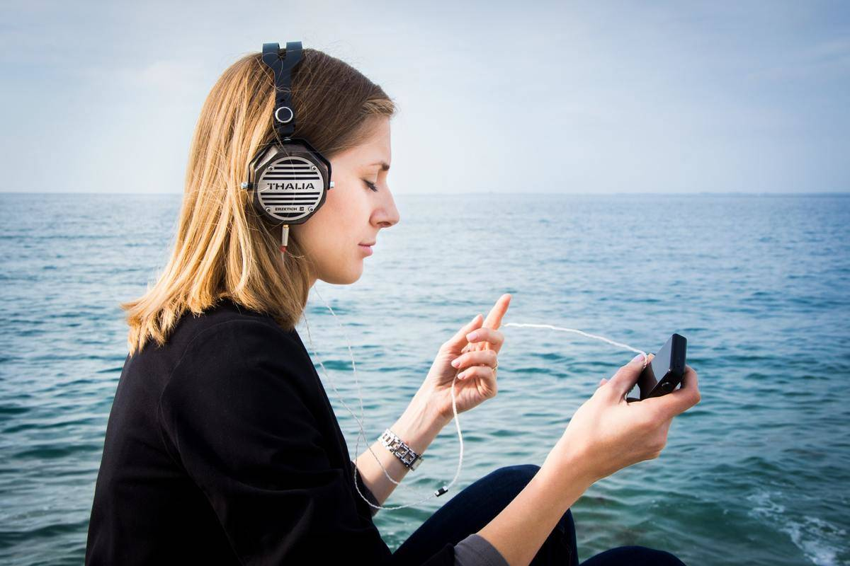 A woman wearing headphones closes her eyes while sitting near the ocean.