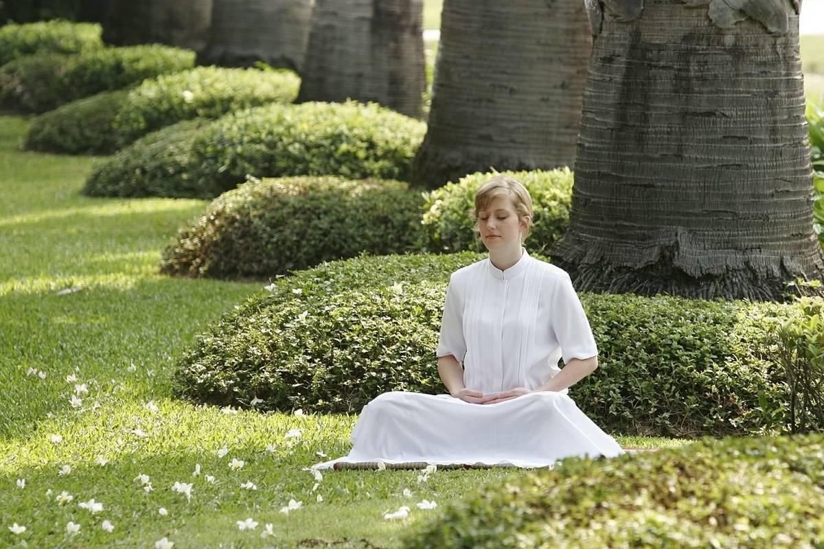 A woman meditates in a Buddhist garden.