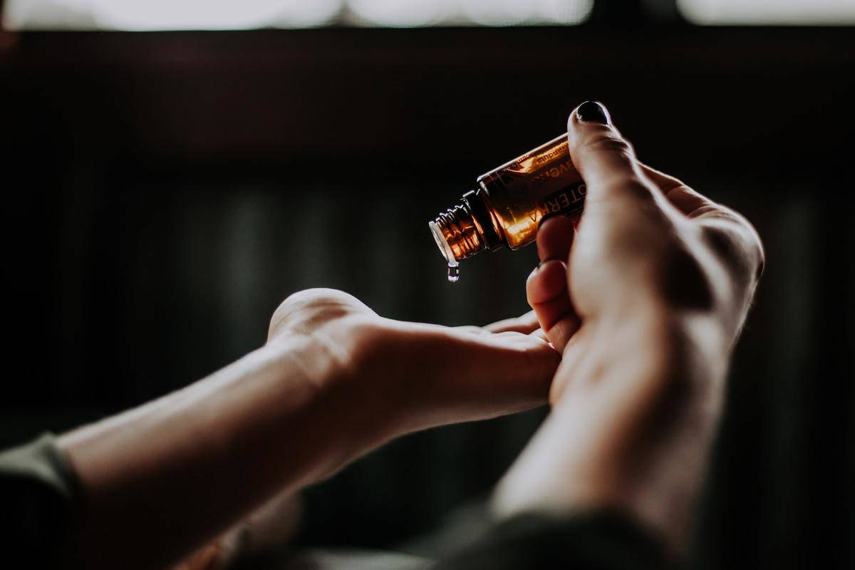 A person places a drip of an essential oil into their palm.
