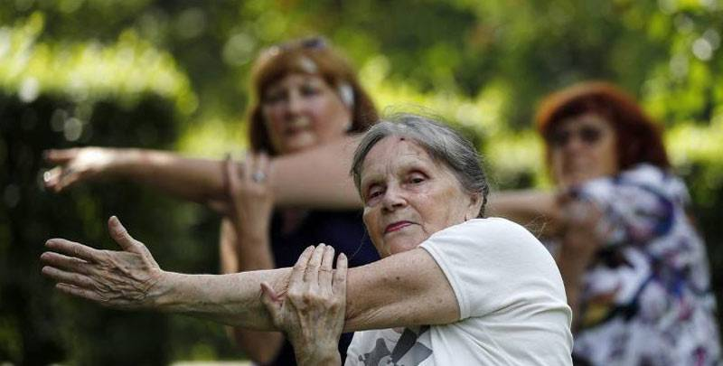 Elderly people practice yoga in a park.
